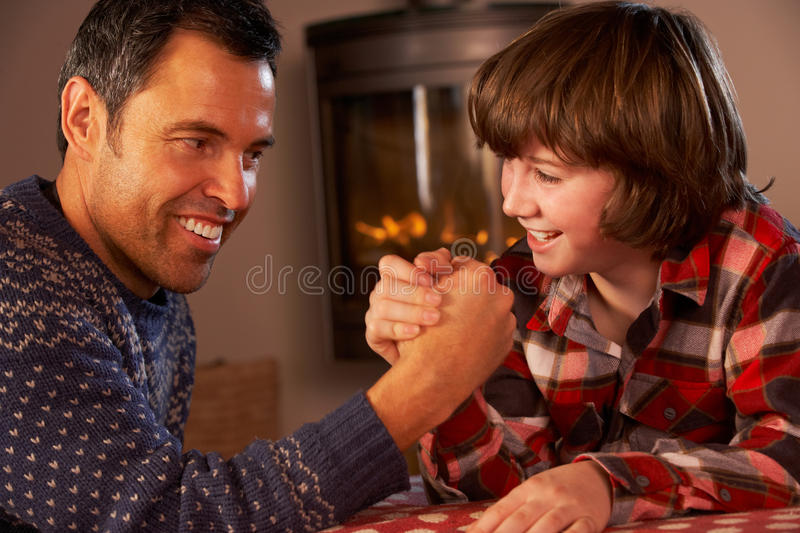 Father And Son Arm Wrestling By Cosy Log Fire. Smiling stock photography