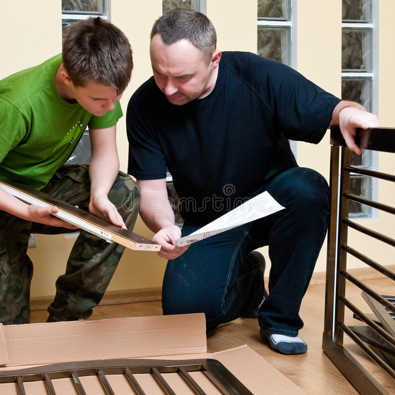 Father and son assemble crib. Father and teenage son assemble new baby bed (cot, crib royalty free stock images
