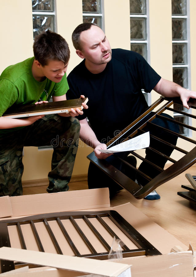 Father and son assemble crib. Father and teenage son assemble new baby bed (cot, crib stock photography