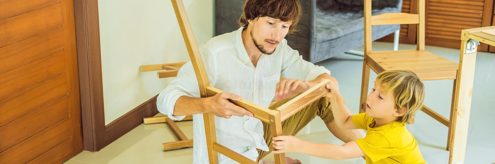 Father and son assembling furniture. Boy helping his dad at home. Happy Family concept BANNER, LONG FORMAT. Father and son assembling furniture. Boy helping his royalty free stock images