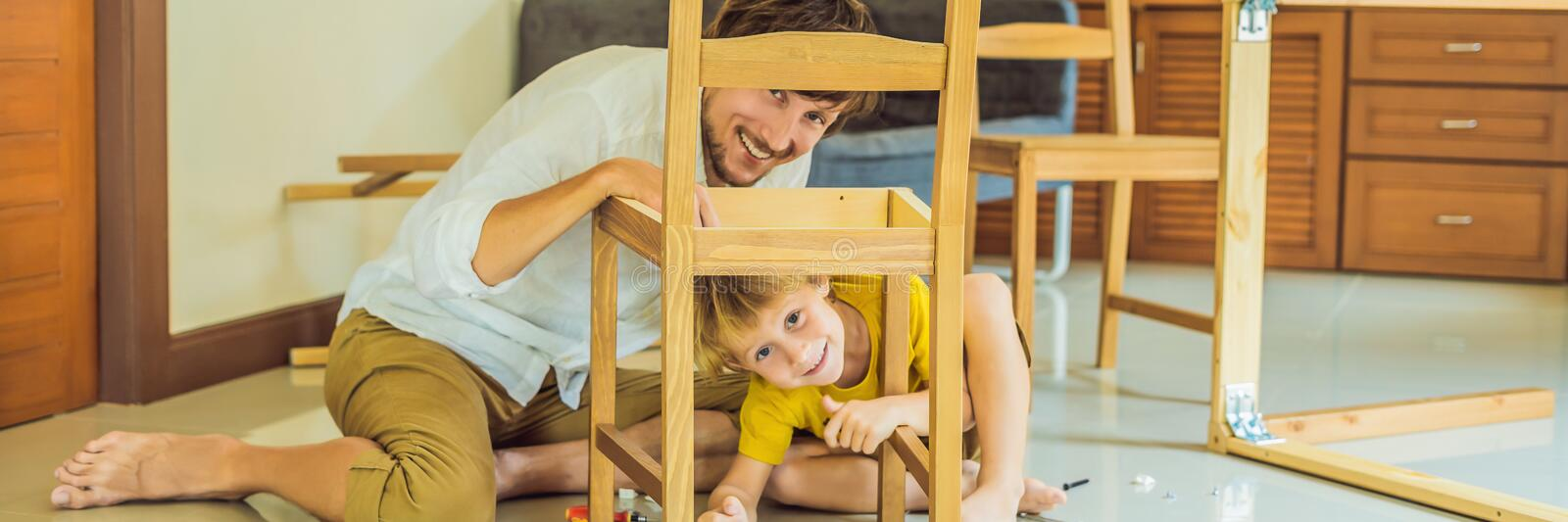 Father and son assembling furniture. Boy helping his dad at home. Happy Family concept BANNER, LONG FORMAT. Father and son assembling furniture. Boy helping his stock photo