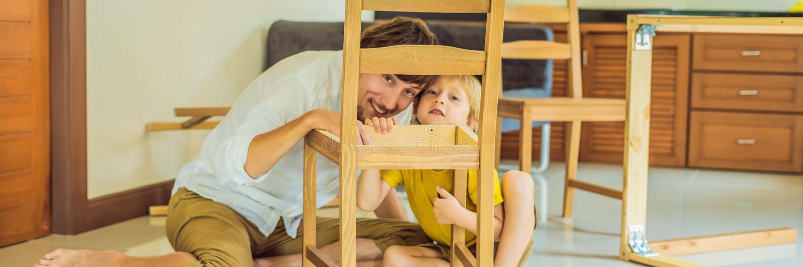 Father and son assembling furniture. Boy helping his dad at home. Happy Family concept BANNER, LONG FORMAT. Father and son assembling furniture. Boy helping his royalty free stock image