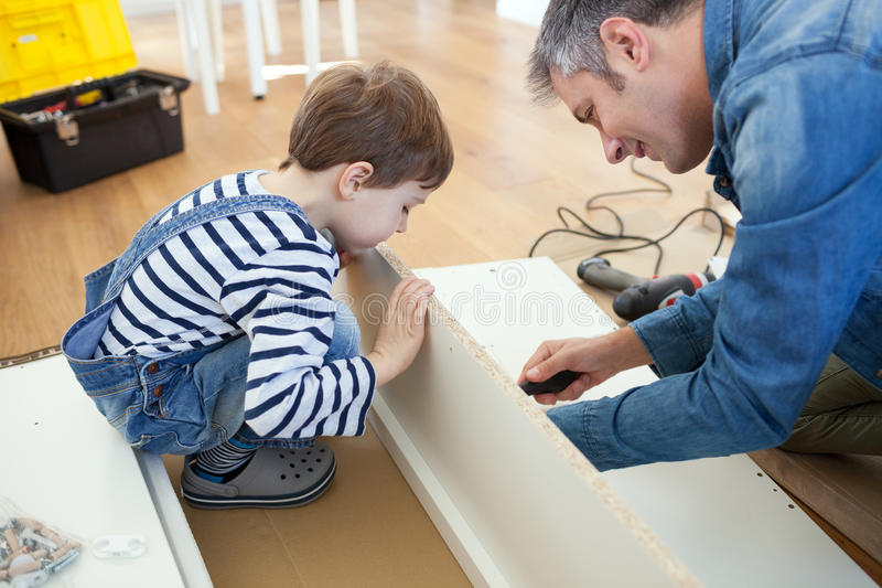 Father and son assembling furniture royalty free stock photography