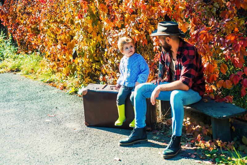 Father and son in autumn park having fun and laughing. stock image