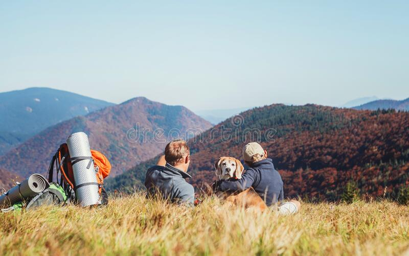 Father and son backpackers hikers resting on mountain hill and enjoying Low Tatras landscape with their beagle dog. Mountain stock photo