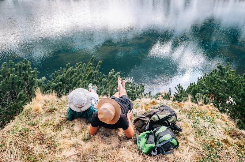 Father and son backpackers relax after long walk near the beautiful lake royalty free stock photos