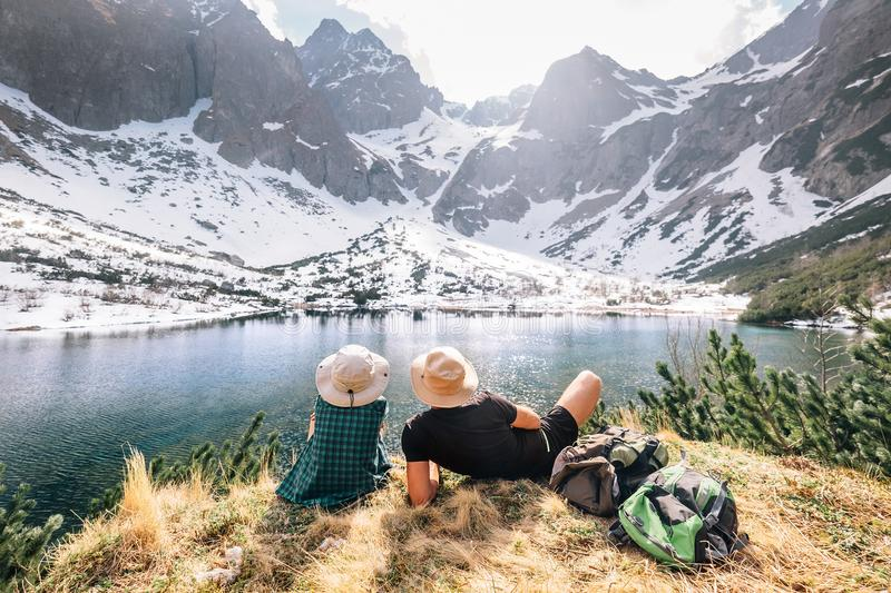 Father and son backpackers sit near the mountain lake and enjoy stock image