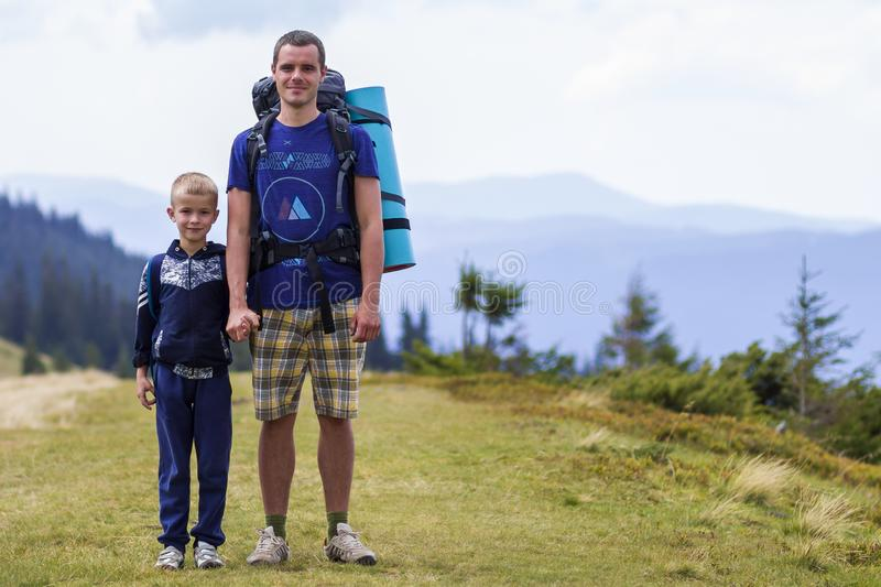 Father and son with backpacks hiking together in scenic summer green mountains. Dad and child standing enjoying landscape mountain stock photos