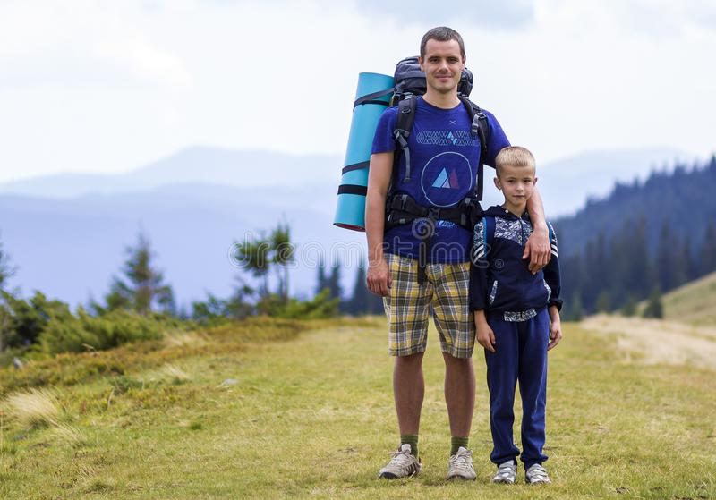 Father and son with backpacks hiking together in scenic summer green mountains. Dad and child standing enjoying landscape mountain stock images