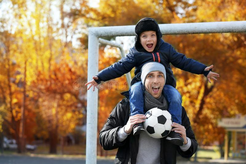 Father and son with ball on soccer pitch royalty free stock images