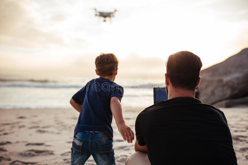 Father and son on the beach flying drone royalty free stock image