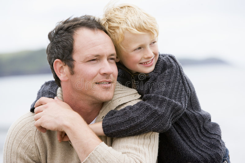Father and son at beach smiling. Away from camera
