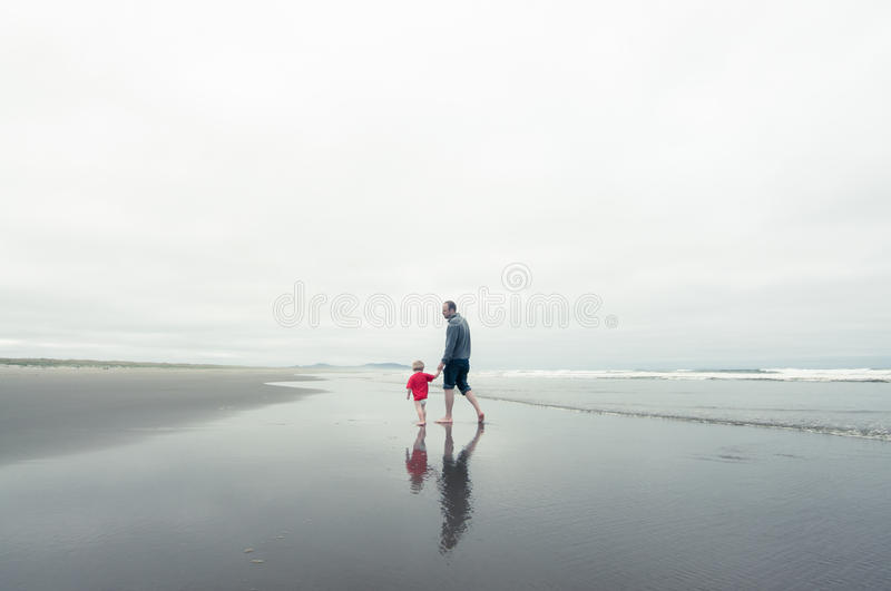 Father and son on the beach in winter royalty free stock images