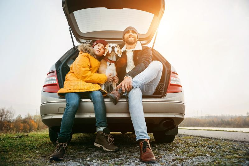 Father and son with beagle dog siting together in car trunk. Long auto journey break stock image