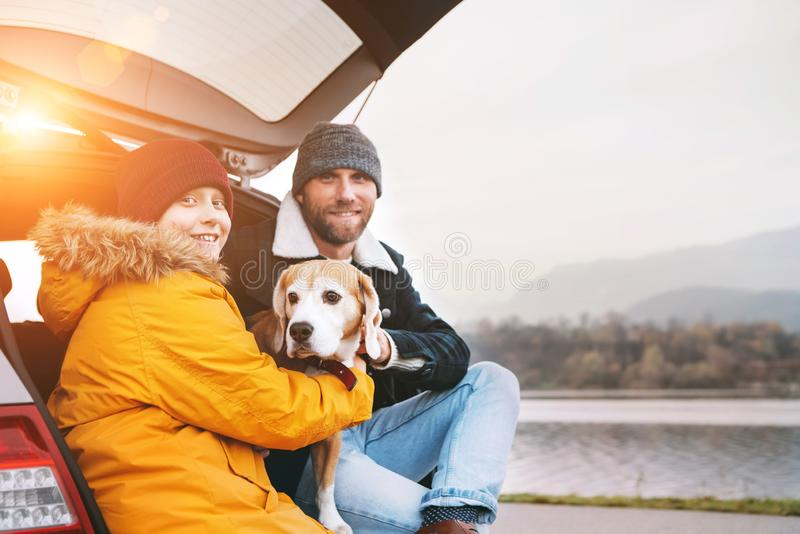 Father and son with beagle dog siting together in car trunk and stock photography