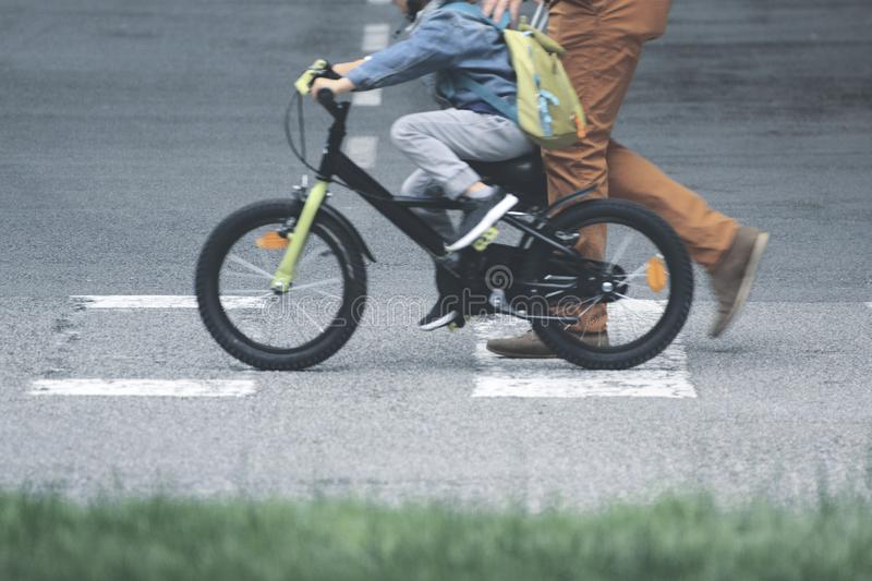 Father and son on a bicycle crossing the walkway to the school. Single parent concept and empty copy space royalty free stock photo