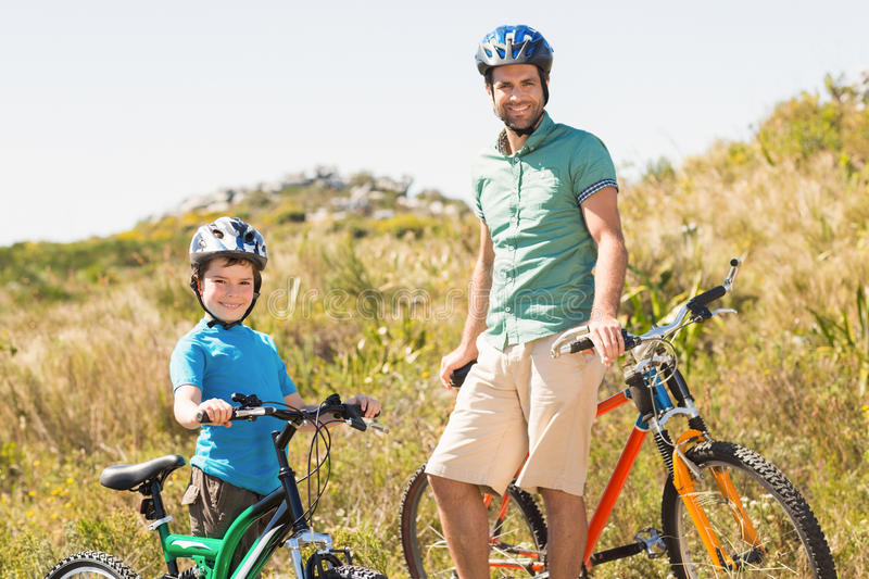 Father and son biking through mountains. On a sunny day royalty free stock photo