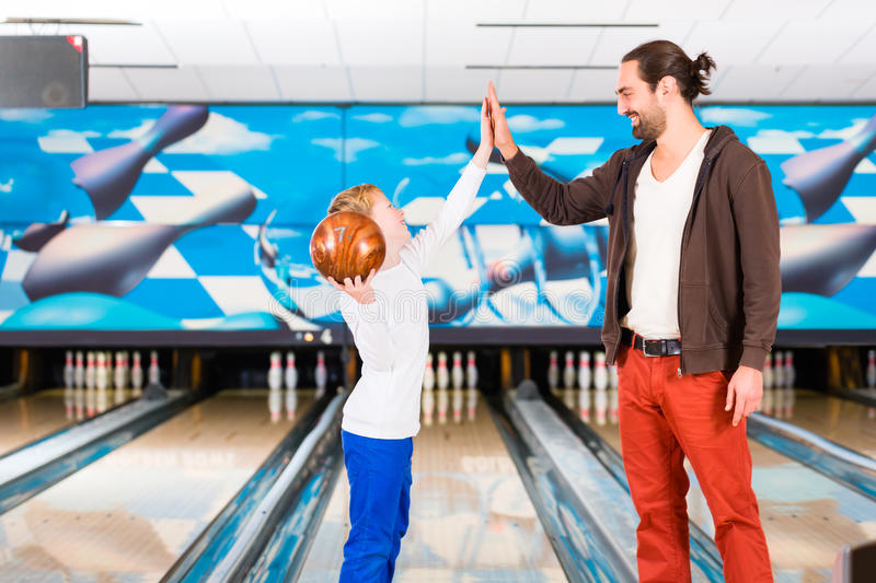 Father and son in bowling center stock photos