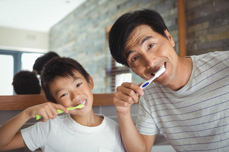 Father and son brushing teeth in the bathroom royalty free stock photography