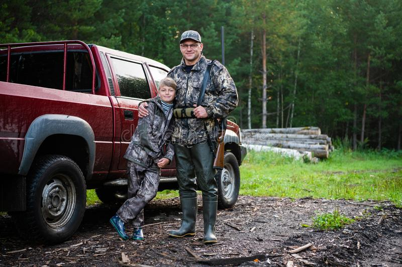 Father and son came to the forest for hunting together. Standing with a shotgun rifle in front of pickup truck. royalty free stock image