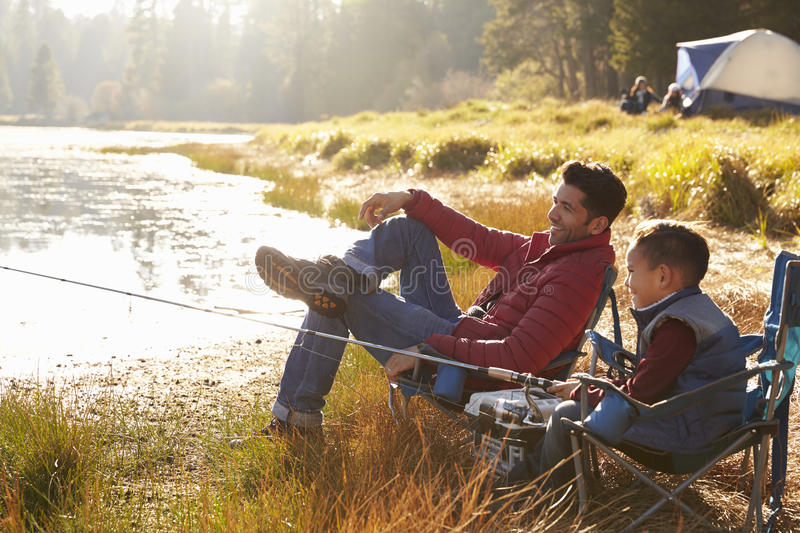 Father and son on a camping trip fishing by a lake stock image