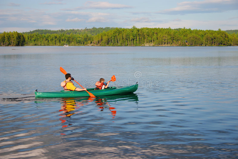 Father and Son Canoeing. Mountain pond. Father and son paddle a canoe