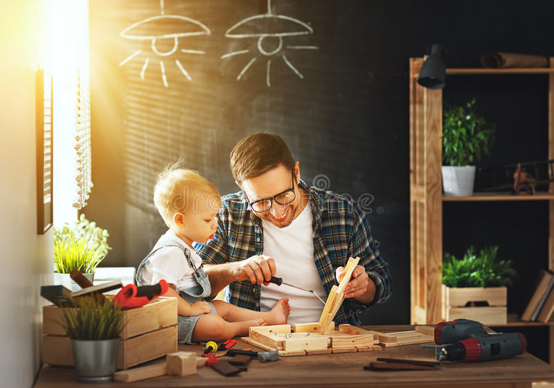 Father and son carved of wood in carpentry workshop royalty free stock photography