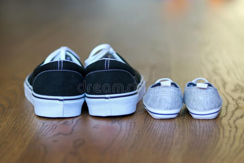 Father and son casual shoes staying next on the wooden floor. Back view. Fathers day stock images