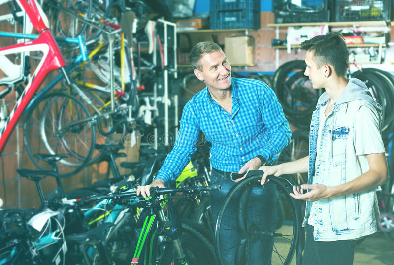 Father and son choosing wheel. Father 40s and his son teenager choosing new wheel lid for bicycle in sport hypermarket royalty free stock images
