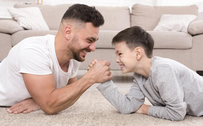 Father and son compete in armwrestling at home. Father and son compete in arm-wrestling, lying on floor at home. Family leisure, panorama stock photo