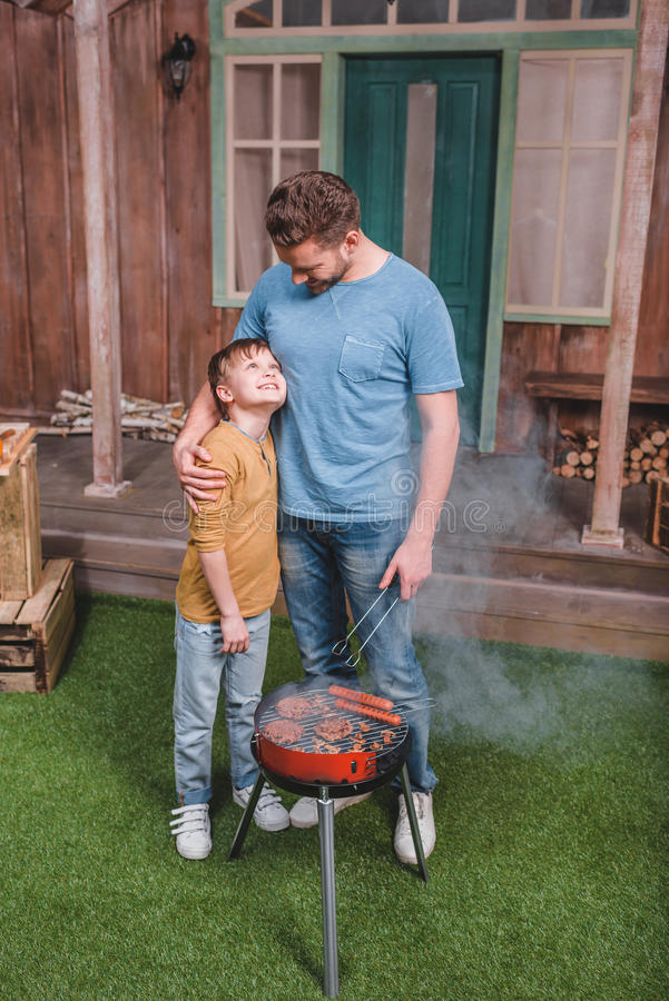 Father and son cooking beef burgers and hot dog sausages on barbecue stock photography