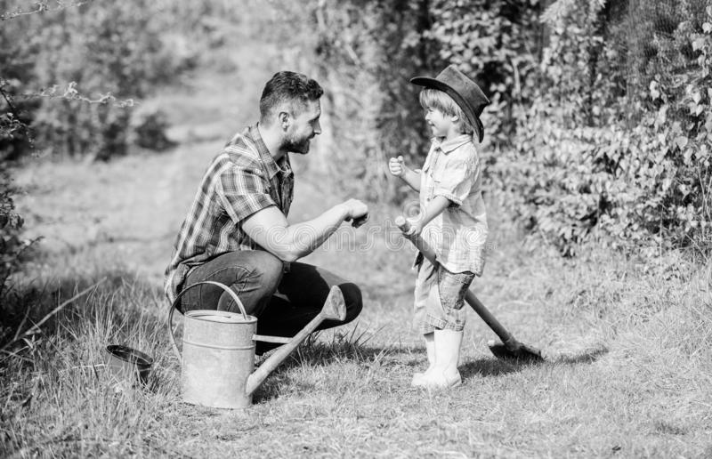 Father and son in cowboy hat on ranch. Eco farm. small boy child help father in farming. watering can, pot and shovel royalty free stock photo