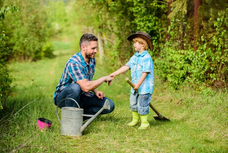 Father and son in cowboy hat on ranch. happy earth day. Family tree nursering. watering can, pot shovel. Garden. Equipment. Eco farm. small boy child help royalty free stock photography