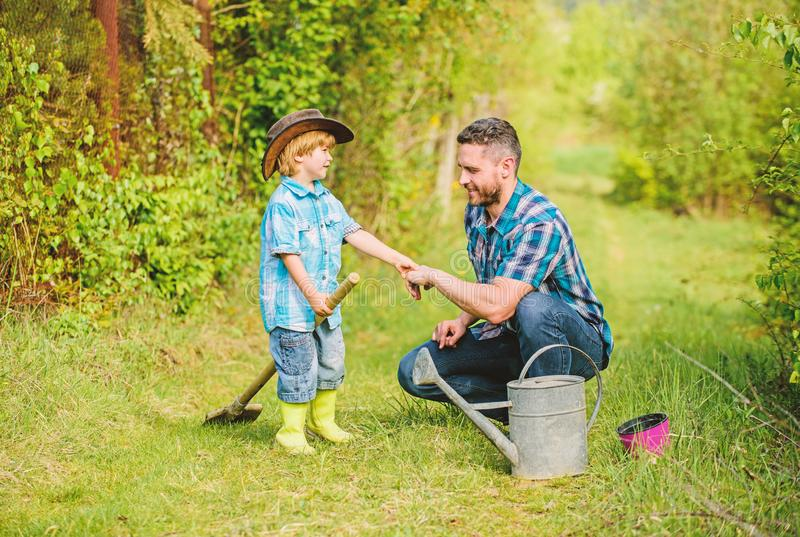 Father and son in cowboy hat on ranch. happy earth day. Family tree nursering. watering can, pot shovel. Garden. Equipment. Eco farm. small boy child help royalty free stock photos