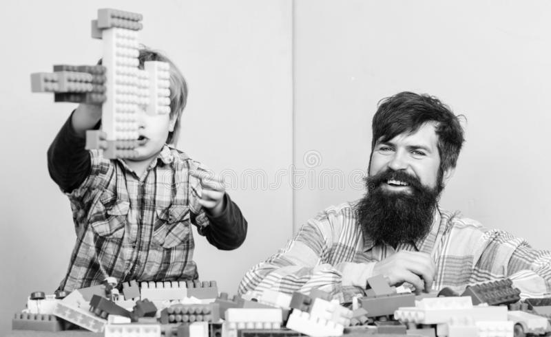 Father son create constructions. Father and boy play together. Dad and kid build plastic blocks. Father leader showing royalty free stock photography