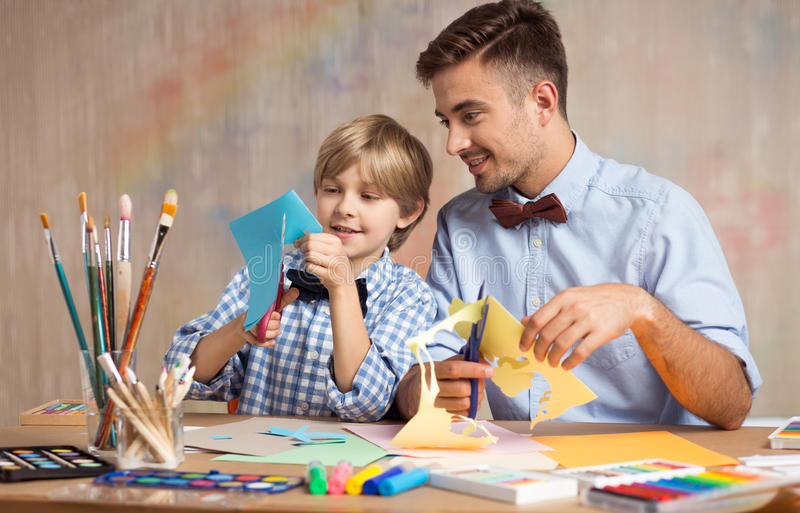 Father and son cutting paper royalty free stock photography