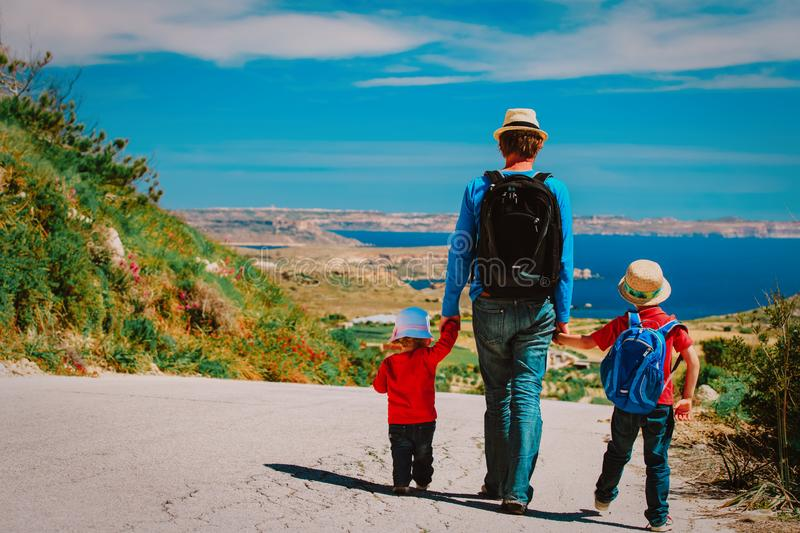 Father with son and daughter walking on scenic road stock photography