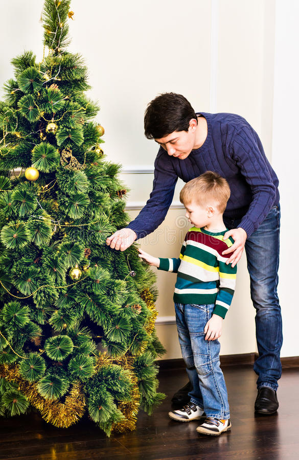 Father and son are decorating the Christmas tree royalty free stock images