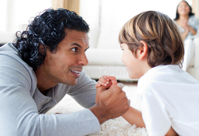 Father and son doing a arm-wrestling on the floor. Supporting by the mother on the background royalty free stock image