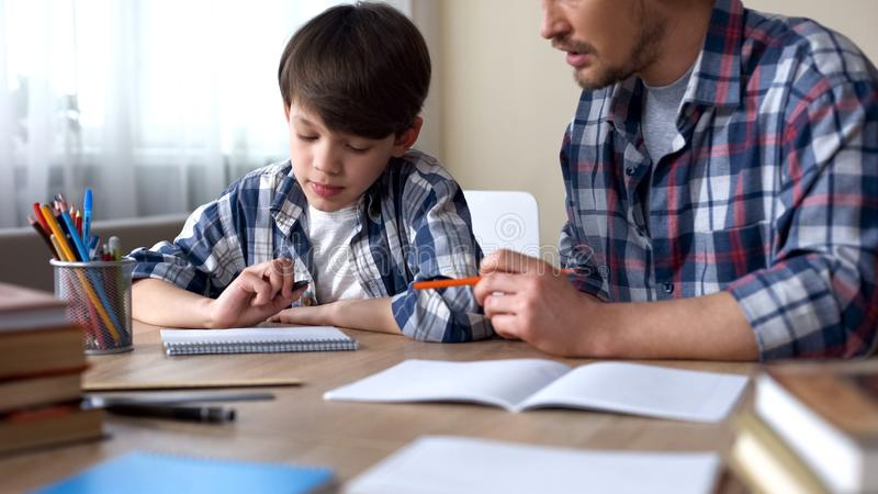Father and son doing homework together, dad explaining task, school education stock image
