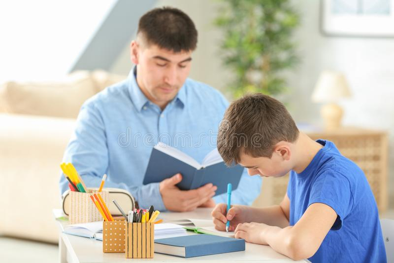 Father and son doing homework together stock photography