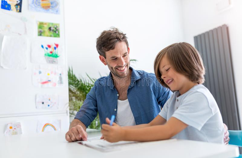 Father and son doing homework together. At home royalty free stock photo