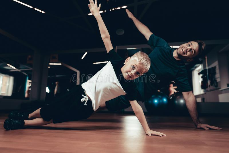 Father And Son Doing Press Exercises In The Gym. royalty free stock photos