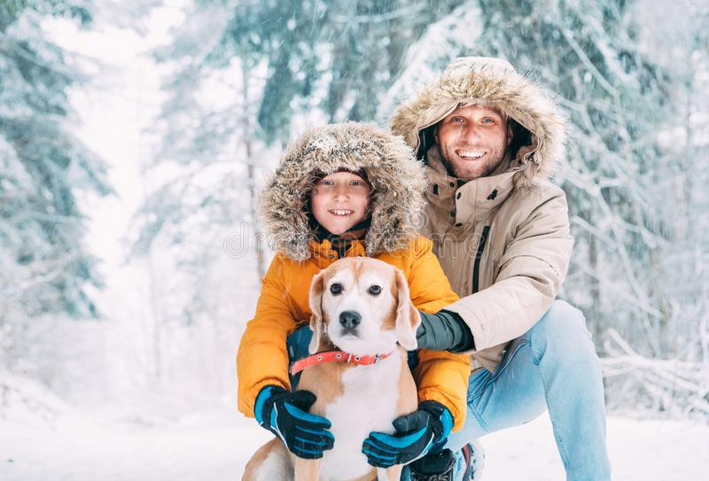 Father and son dressed in Warm Hooded Casual Parka Jacket Outerwear walking with their beagle dog in snowy forest cheerful. Smiling faces portrait. Pets in royalty free stock photos