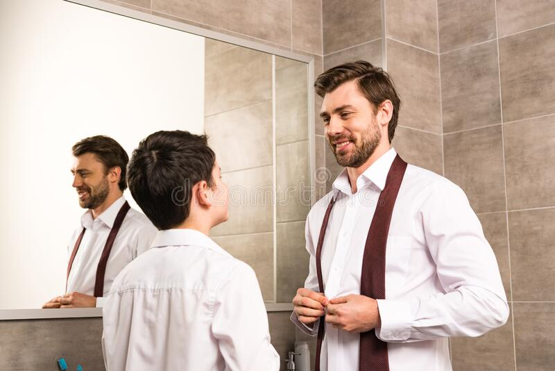Father and son dressing in formal wear. In bathroom stock photography