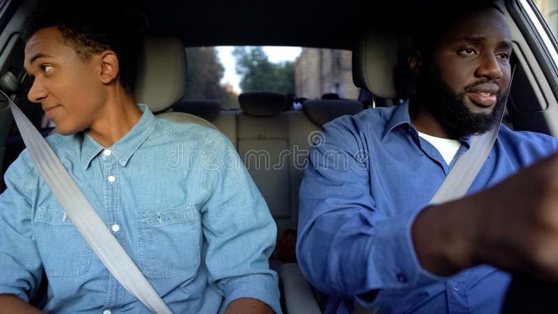 Father and son driving in automobile, guy looking in window, misunderstanding stock photos