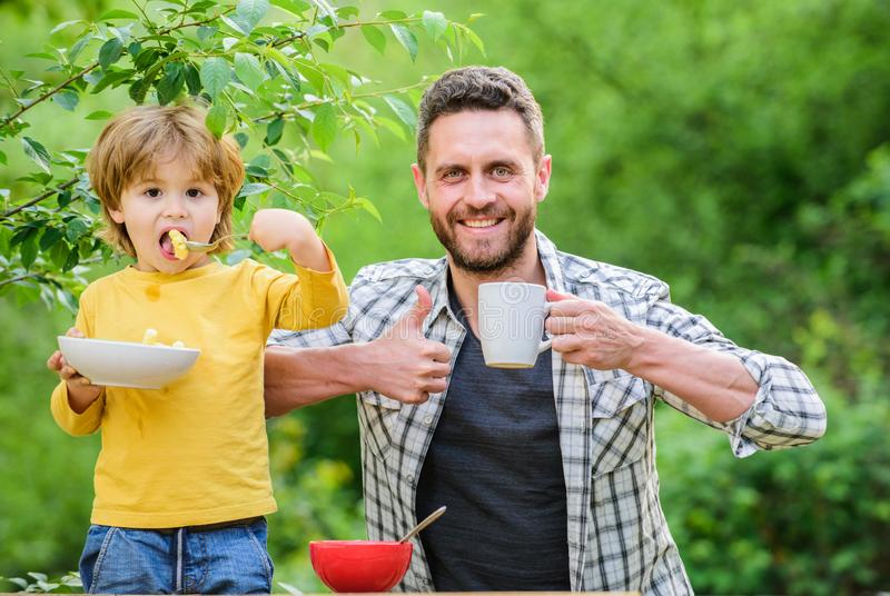 Father son eat food and have fun. Little boy and dad eating. Nutrition for kids and adults. Healthy nutrition concept stock photography