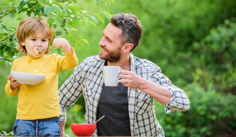 Father son eat food and have fun. Little boy and dad eating. Nutrition kids and adults. Healthy nutrition concept. Menu royalty free stock image