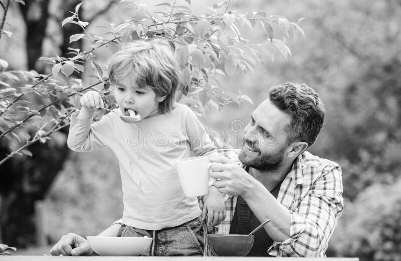 Father son eat food and have fun. Menu for children. Family enjoy homemade meal. Food habits. Little boy with dad eating stock image