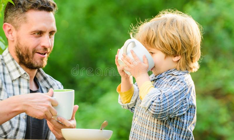 Father and son eat outdoor. healthy food. Family day bonding. small boy child with dad. they love eating together. Weekend breakfast. organic and natural food stock photo